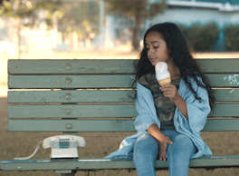 Photo image: Young girl on outdoor bench looking at a handset telephone